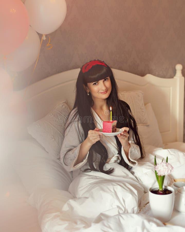 La muchacha come el desayuno en cama Cumpleaños foto de archivo libre de regalías