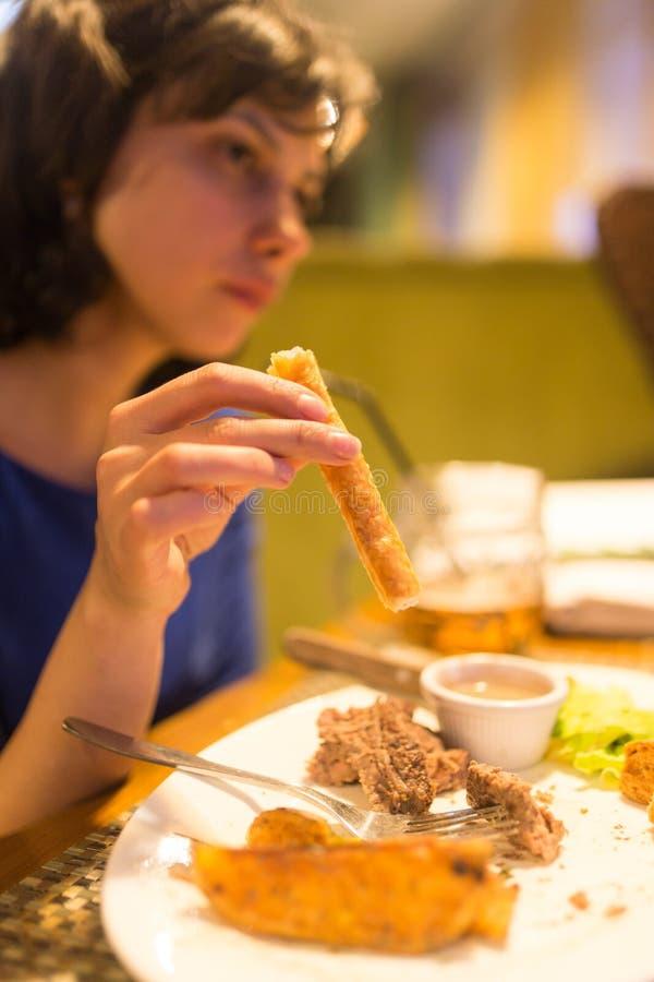 La muchacha come el pan en el restaurante fotos de archivo