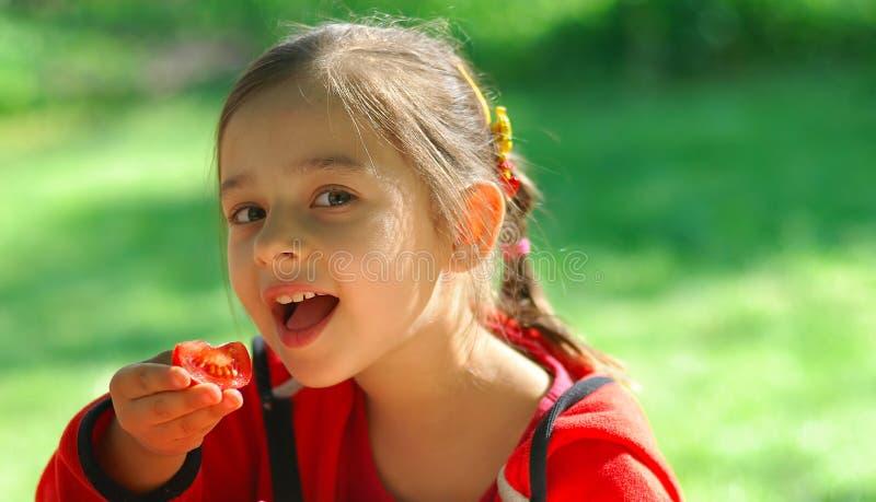 La muchacha come el tomate imagenes de archivo
