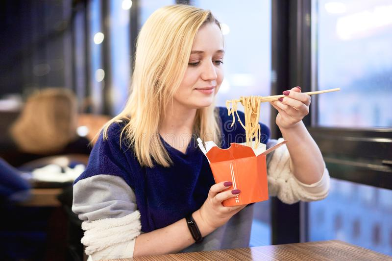 La muchacha come el wok en la comida Kurt Mujer hermosa que come los tallarines tailandeses en la caja de papel para llevar fotografía de archivo