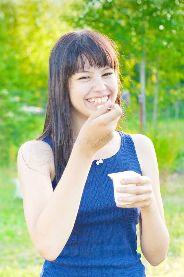 La muchacha come el yogur foto de archivo libre de regalías