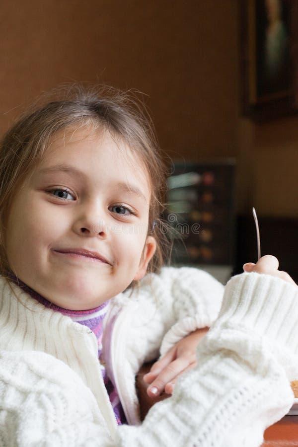 La muchacha come en el café fotografía de archivo