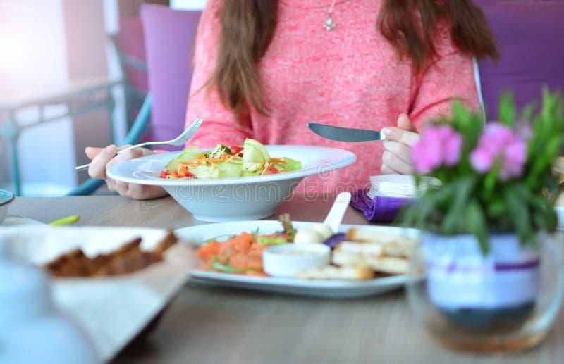 La muchacha come la ensalada vegetal imagen de archivo libre de regalías