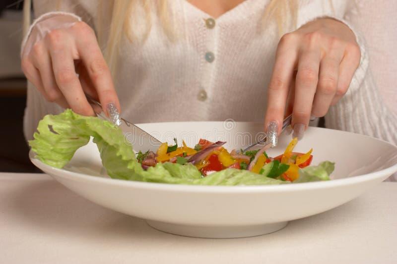 La muchacha come la ensalada foto de archivo