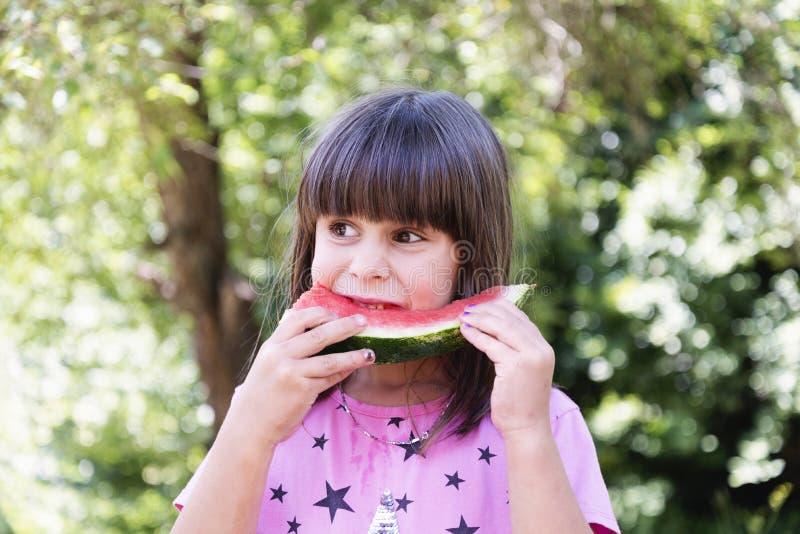 La muchacha come la sandía al aire libre imágenes de archivo libres de regalías