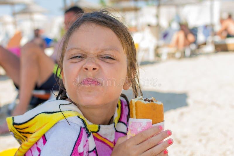 La muchacha come un buñuelo en la playa imagen de archivo libre de regalías