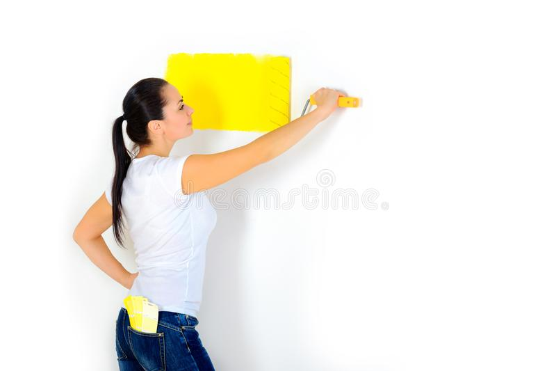 La muchacha comenzó a pintar las paredes foto de archivo