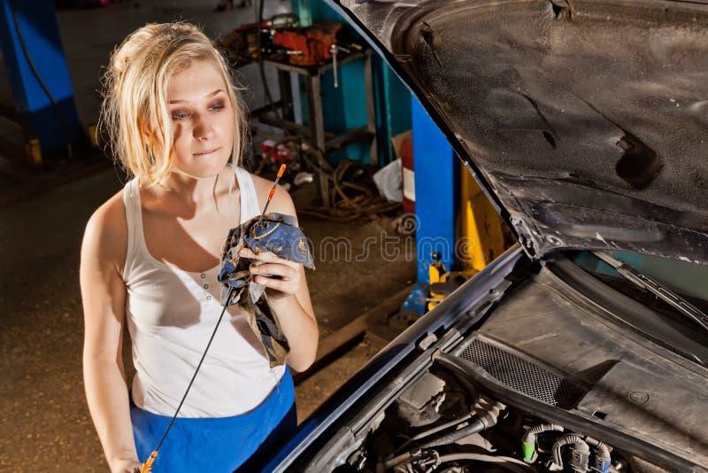 La muchacha comprueba el nivel de aceite en el coche foto de archivo