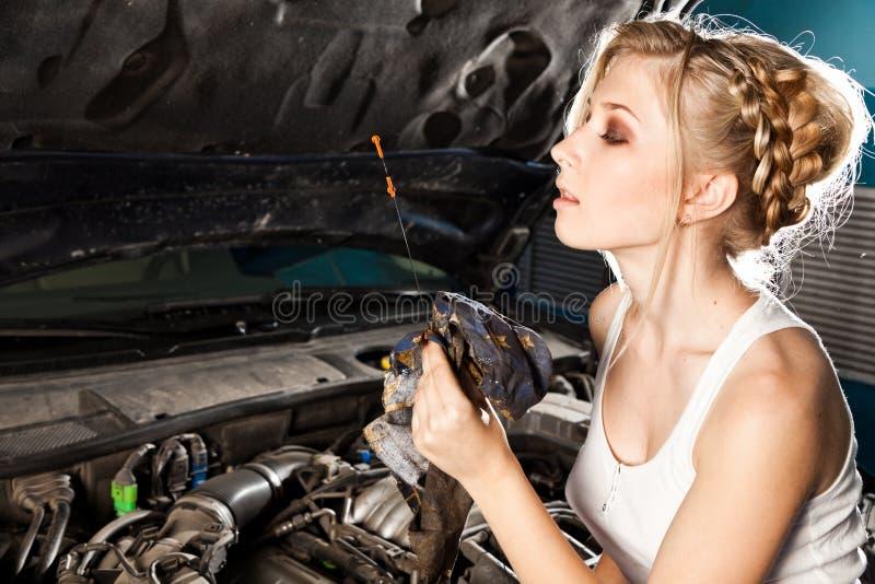 La muchacha comprueba el nivel de aceite en el coche imagenes de archivo