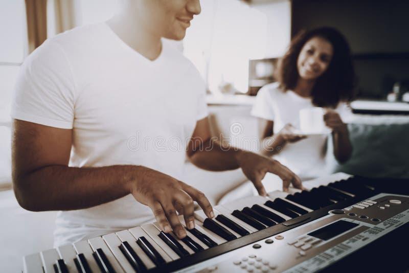 La muchacha con café escucha juego del sintetizador del ` s del hombre imagenes de archivo