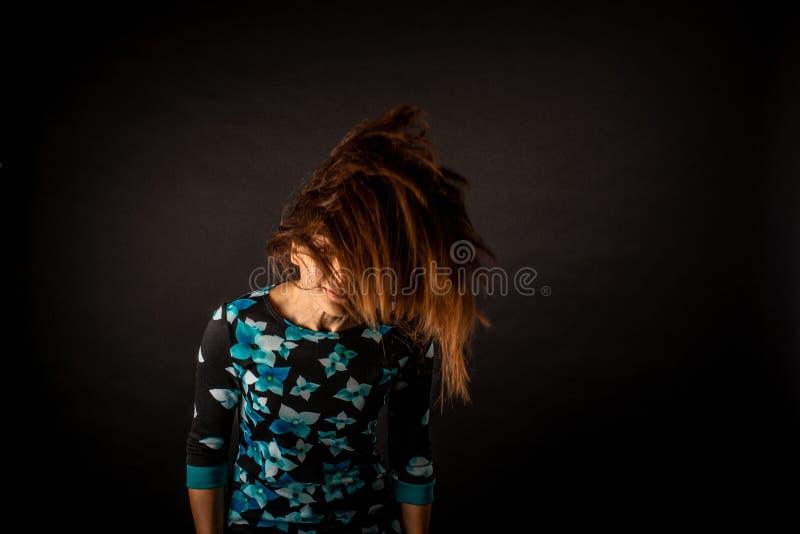 La muchacha con desarrollar el pelo largo en fondo negro fotografía de archivo