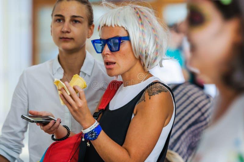La muchacha con el peinado original, las gafas de sol azules que llevaban comiendo la GOMA calificó el helado imágenes de archivo libres de regalías