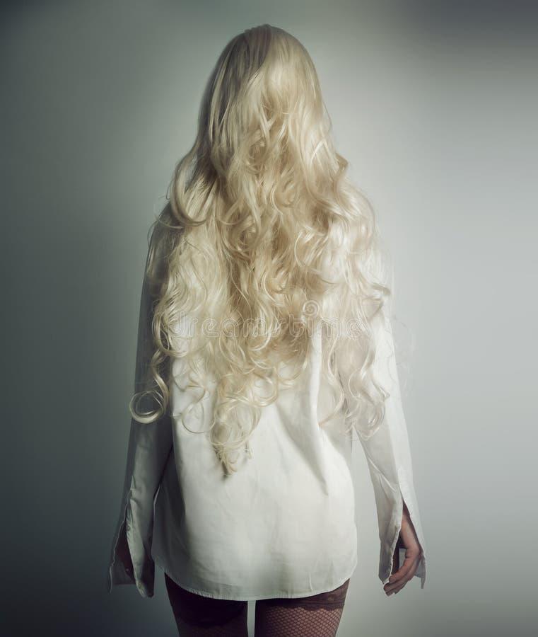La muchacha con el pelo blanco en una camisa blanca se coloca foto de archivo
