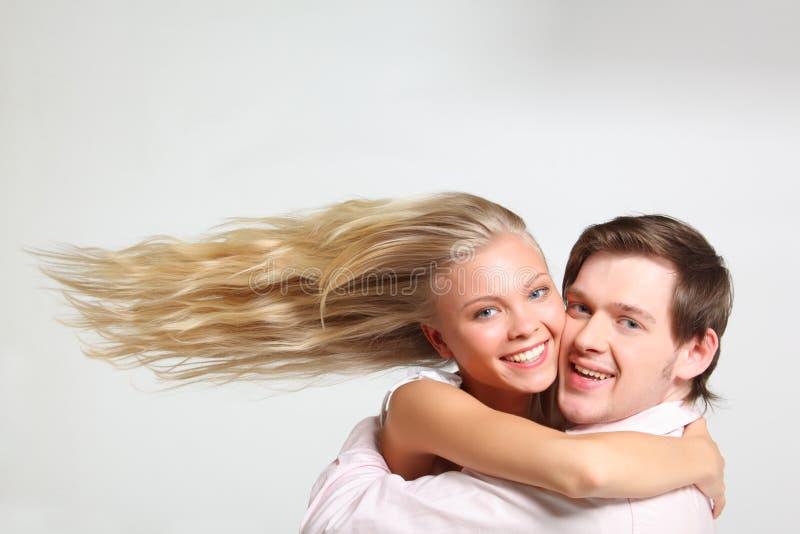 La muchacha con el pelo del vuelo abraza al hombre joven fotografía de archivo