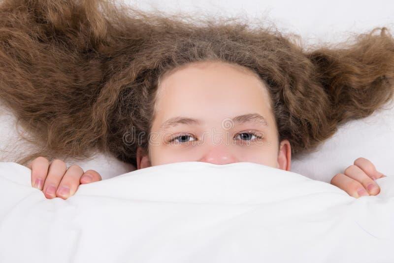La muchacha con el pelo despeinado en una cama oculta debajo de ojos de una manta es visible fotografía de archivo