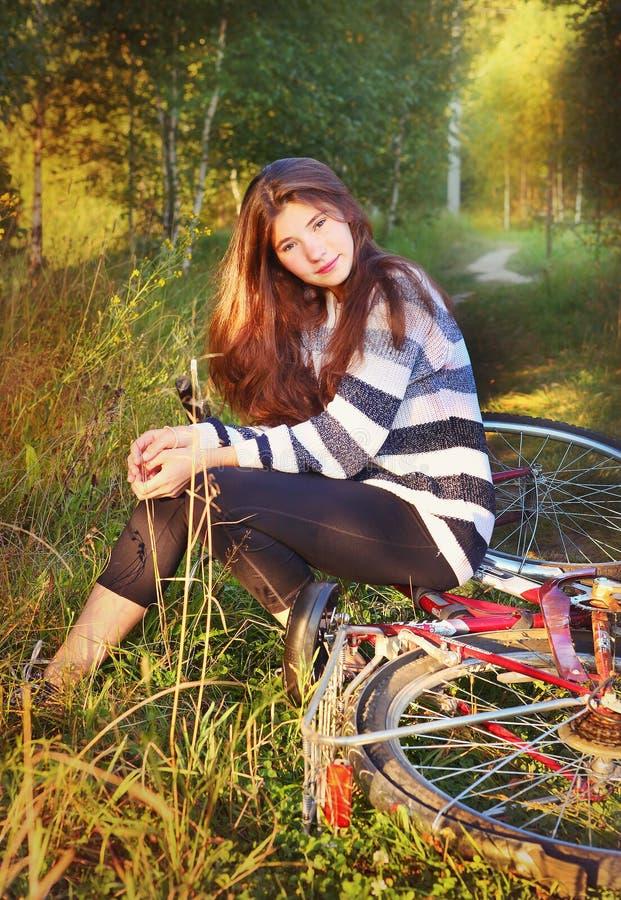 La muchacha con el pelo flojo marrón largo se sienta en la bicicleta imagenes de archivo