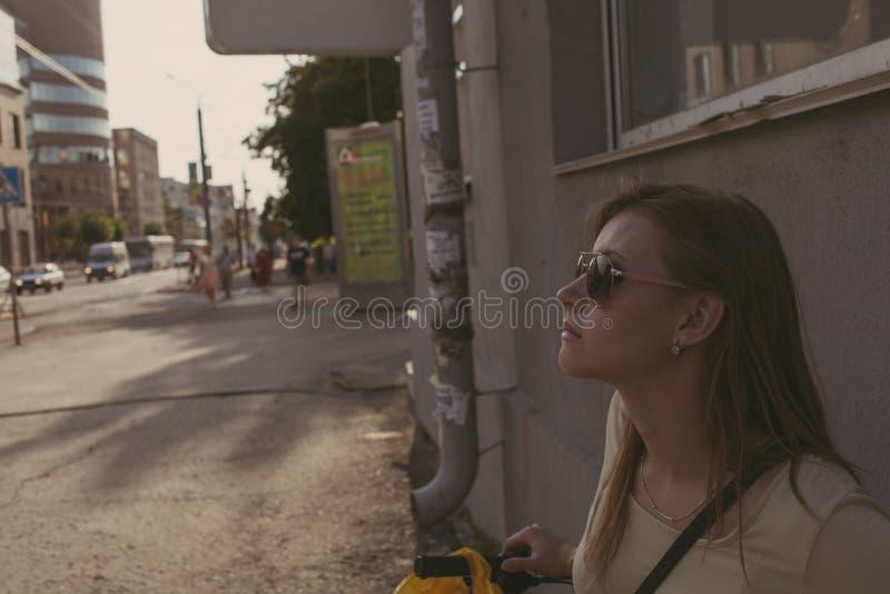 La muchacha con el pelo que fluye en gafas de sol se opone a una pared en la ciudad imagenes de archivo