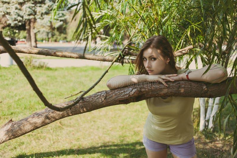 La muchacha con el pelo que fluye en pantalones cortos cortos se coloca cerca de un árbol en un fondo del verdor fotos de archivo libres de regalías