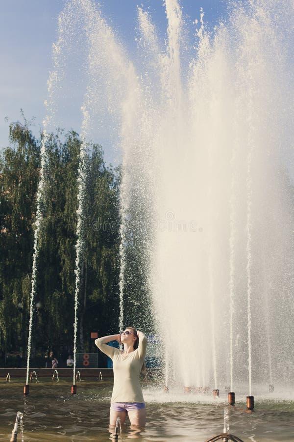 La muchacha con el pelo que fluye en pantalones cortos cortos y gafas de sol se est? colocando en la fuente foto de archivo