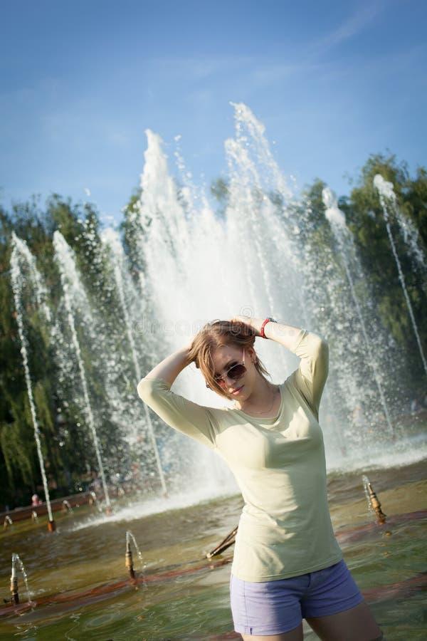 La muchacha con el pelo que fluye en pantalones cortos cortos y gafas de sol se est? colocando en la fuente imagen de archivo libre de regalías