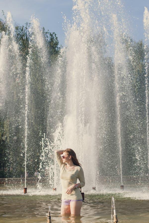 La muchacha con el pelo que fluye en pantalones cortos cortos y gafas de sol se est? colocando en la fuente imágenes de archivo libres de regalías