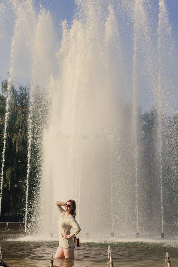 La muchacha con el pelo que fluye en pantalones cortos cortos y gafas de sol se est? colocando en la fuente fotografía de archivo