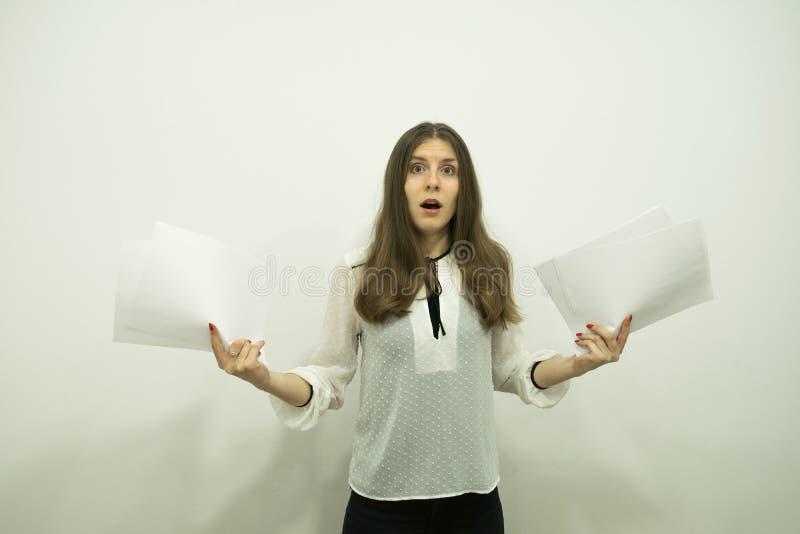 La muchacha con el pelo que fluye se coloca en el centro del bastidor, sosteniendo las hojas blancas en sus manos y muy se sorpre fotografía de archivo libre de regalías