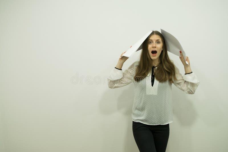 la muchacha con el pelo que fluye y la boca abierta en choque se está colocando a la derecha que sostiene las hojas blancas en su fotos de archivo libres de regalías