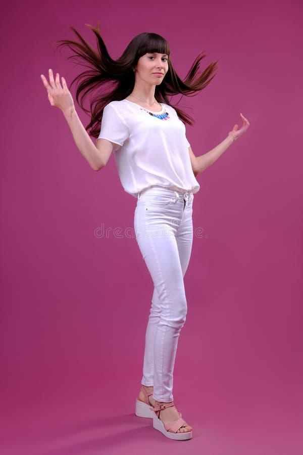 La muchacha con el pelo que se convierte se fotografía en estudio en un fondo rosado fotos de archivo libres de regalías