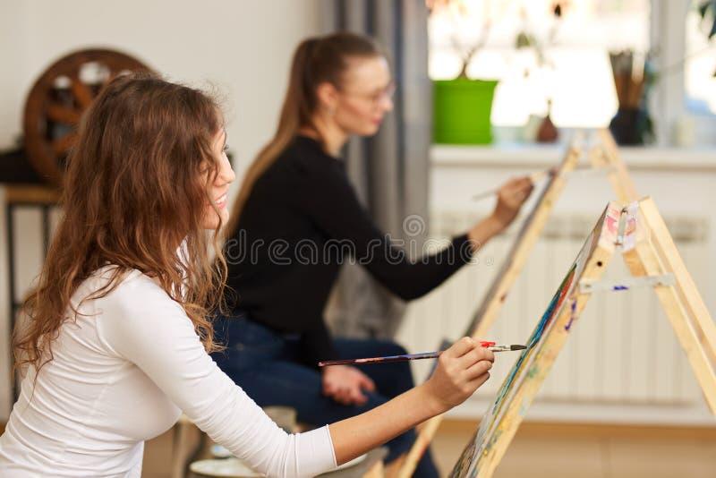 La muchacha con el pelo rizado marr?n vestido en la blusa blanca pinta una imagen en el caballete en la escuela de dibujo fotografía de archivo