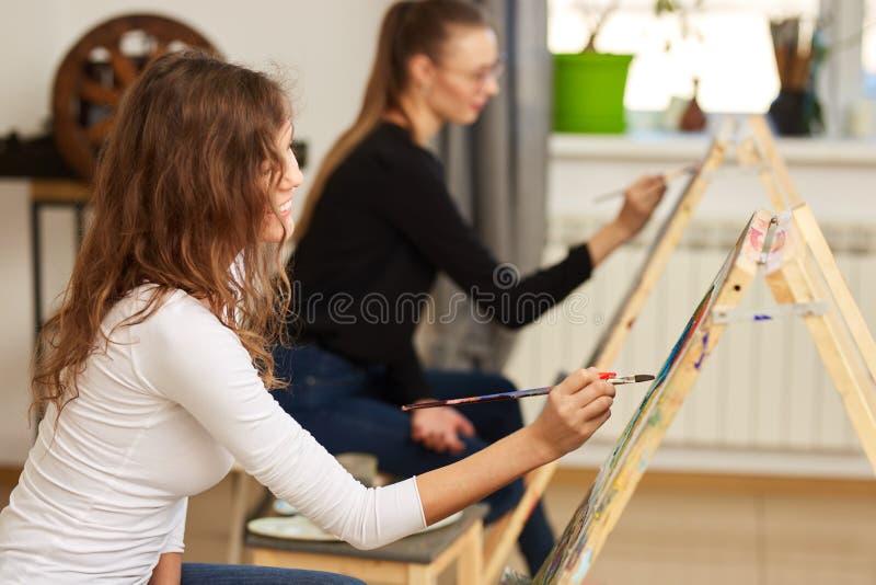 La muchacha con el pelo rizado marr?n vestido en la blusa blanca pinta una imagen en el caballete en la escuela de dibujo fotos de archivo