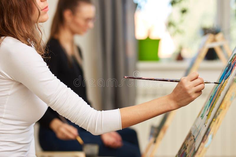 La muchacha con el pelo rizado marr?n vestido en la blusa blanca pinta una imagen en el caballete en la escuela de dibujo fotografía de archivo libre de regalías