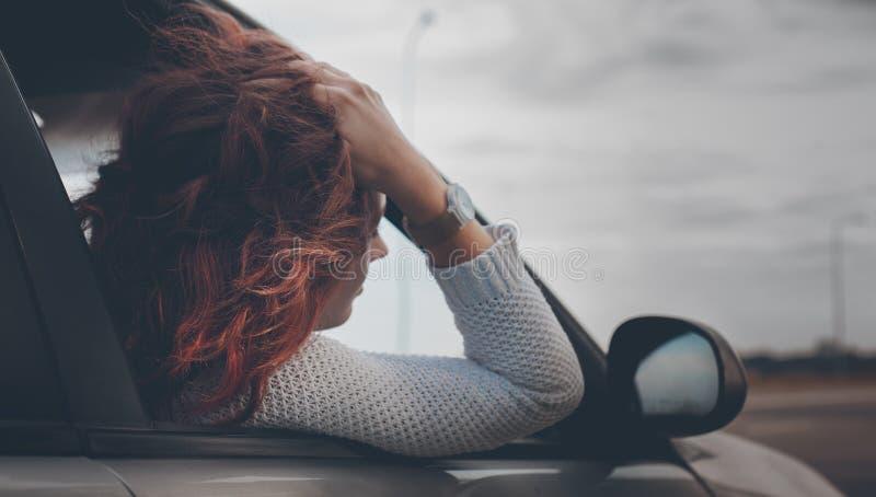 La muchacha con el pelo rojo en un suéter hecho punto blanco con un reloj en su mano mira hacia fuera la ventana foto de archivo