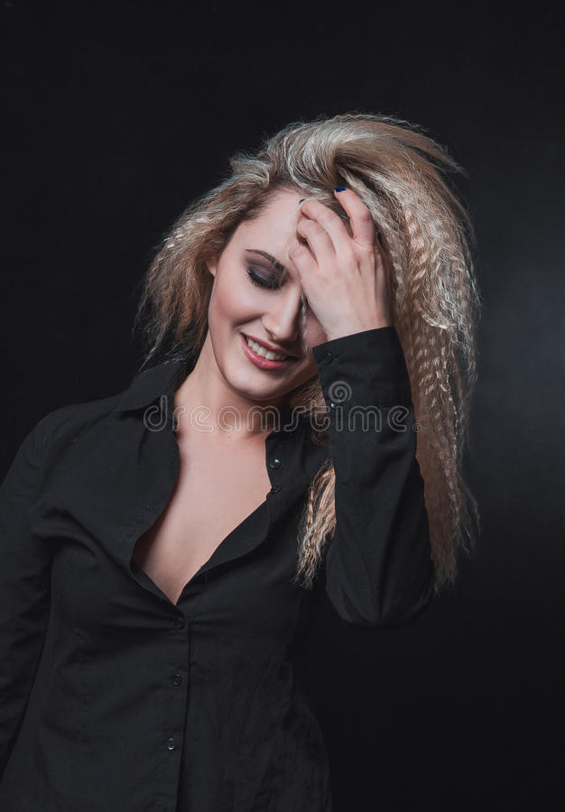 La muchacha con el pelo rubio en fondo negro fotografía de archivo