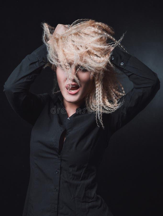 La muchacha con el pelo rubio en fondo negro imagen de archivo