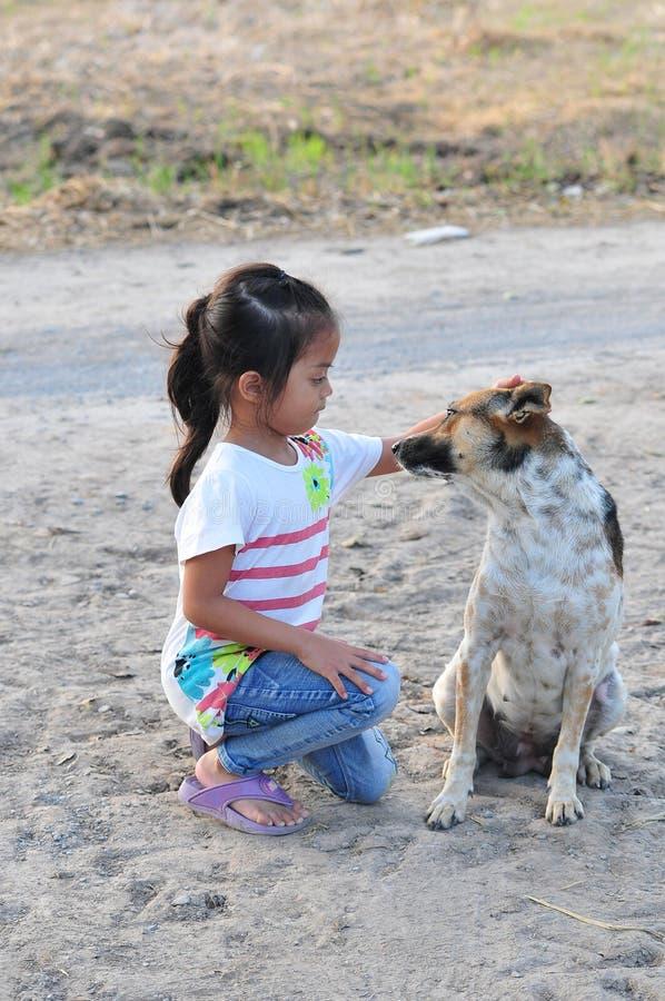 La muchacha con el perro marrón y blanco en el campo en Tailandia rural imágenes de archivo libres de regalías