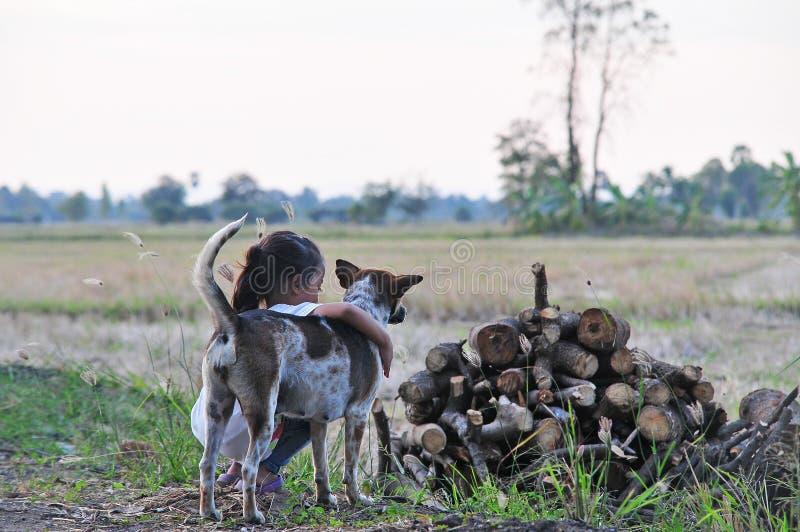 La muchacha con el perro marrón y blanco en el campo en Tailandia rural fotos de archivo