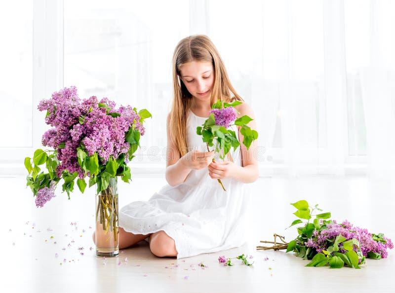 La muchacha con el ramo de lila florece sentarse en el piso imagenes de archivo