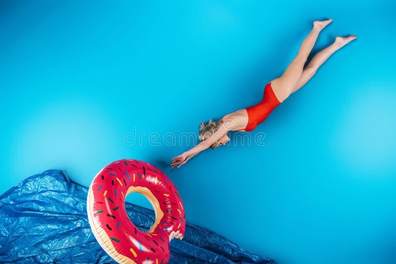 la muchacha con el salto del anillo de la natación adentro se imagina el mar en el azul, verano foto de archivo