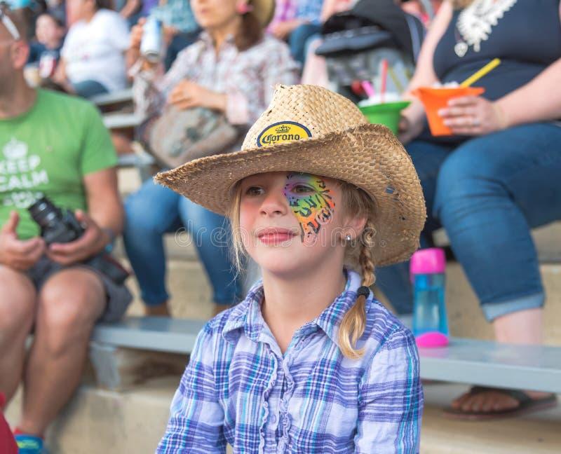 La muchacha con el sombrero de vaquero de la pintura colorida de la cara que lleva mira a Williams Lake Stampede imagen de archivo libre de regalías