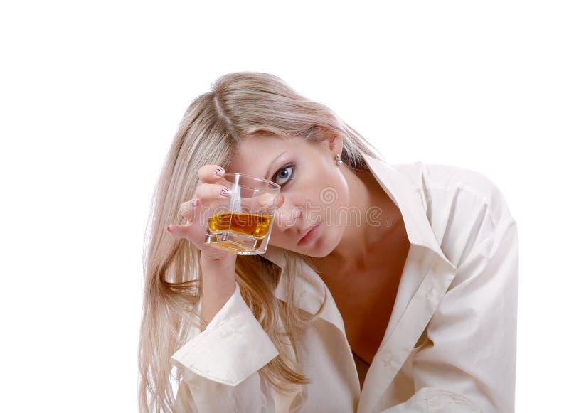 La muchacha con el vidrio de whisky en un blanco fotografía de archivo libre de regalías
