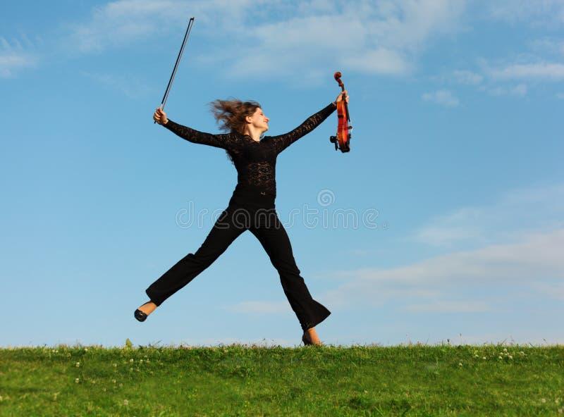 La muchacha con el violín salta contra el cielo fotografía de archivo libre de regalías