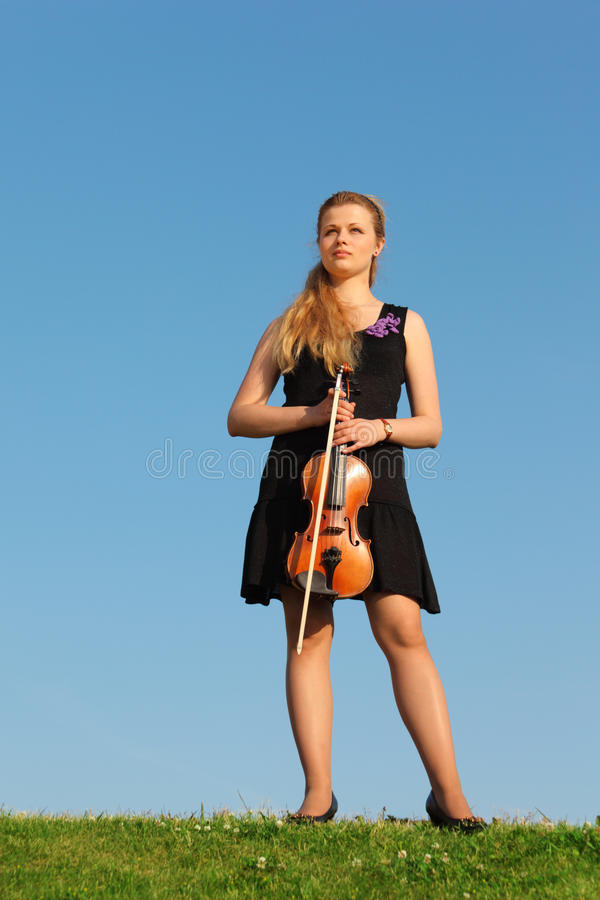 La muchacha con el violín se opone en hierba al cielo imagen de archivo
