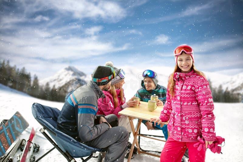 La muchacha con la familia en café en terreno del esquí goza foto de archivo libre de regalías
