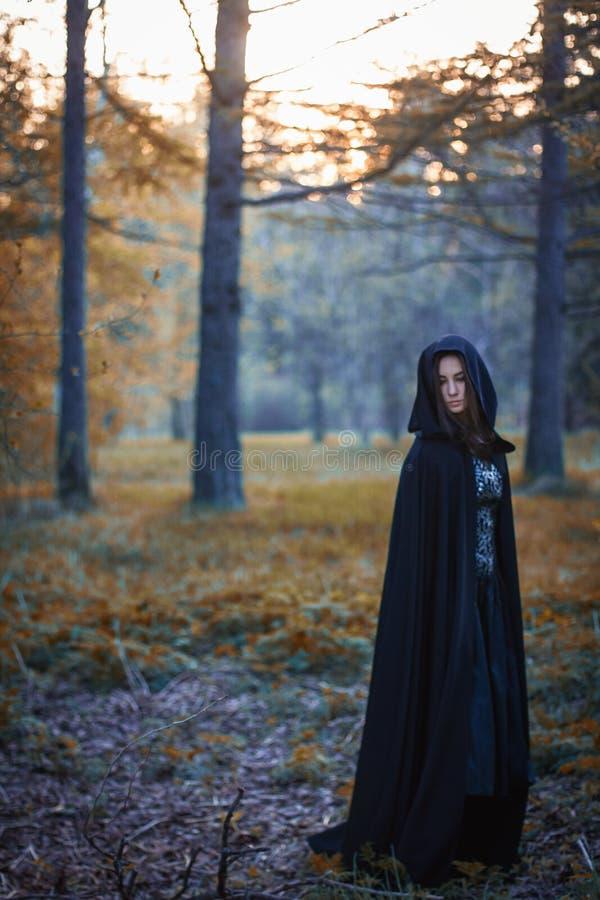 La muchacha con la capa negra en el bosque imagenes de archivo