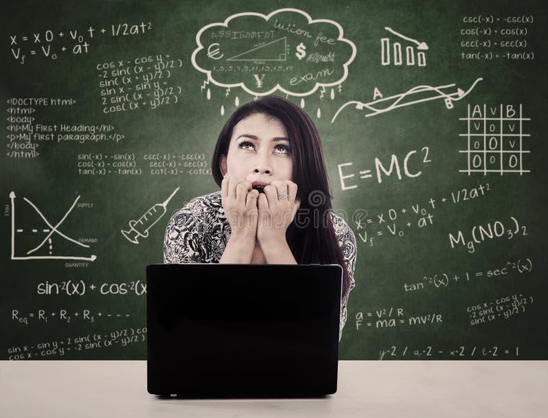 La muchacha con la computadora portátil es examen nervioso de la cara fotos de archivo