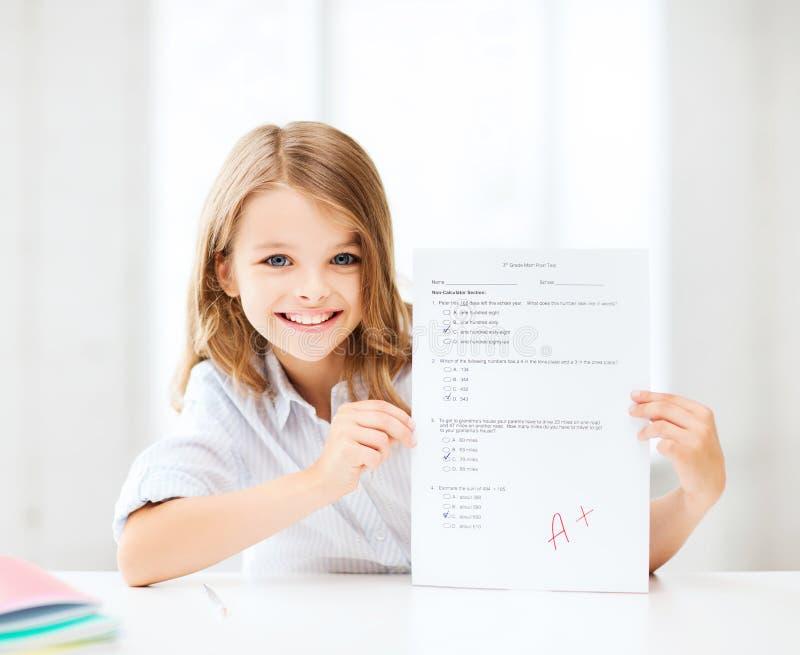 La muchacha con la prueba y A califican en la escuela fotografía de archivo libre de regalías