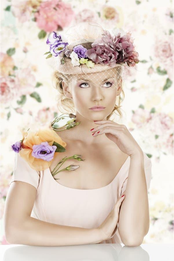 La muchacha con las flores en el sombrero mira para arriba fotografía de archivo