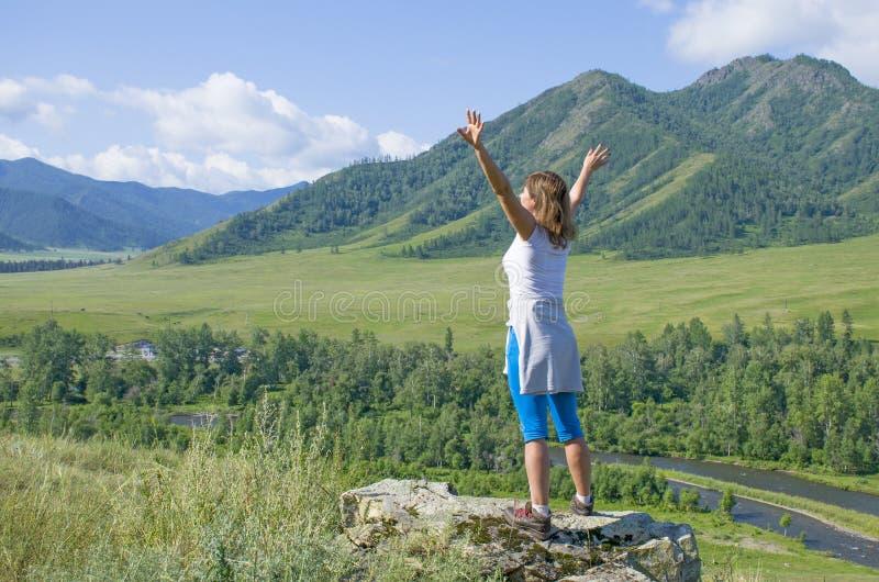 La muchacha con las manos aumentadas en las montañas Altai Rusia la visión superior imagen de archivo