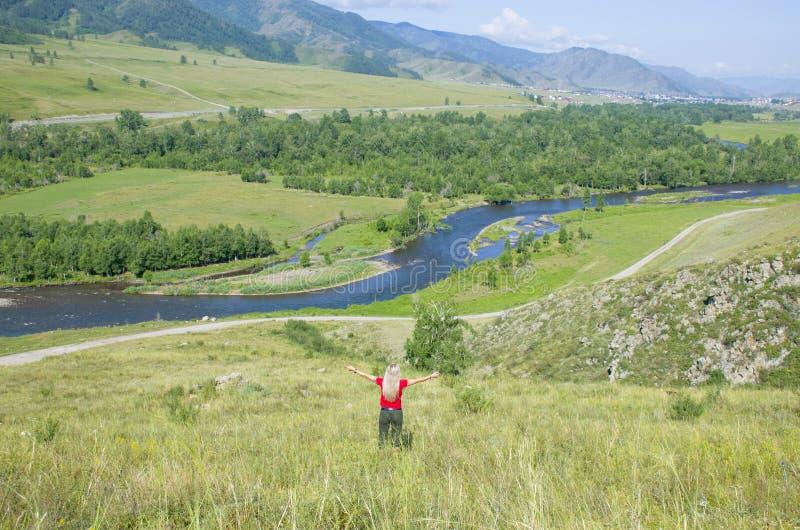 La muchacha con las manos aumentadas en las montañas Altai Rusia la visión superior foto de archivo libre de regalías